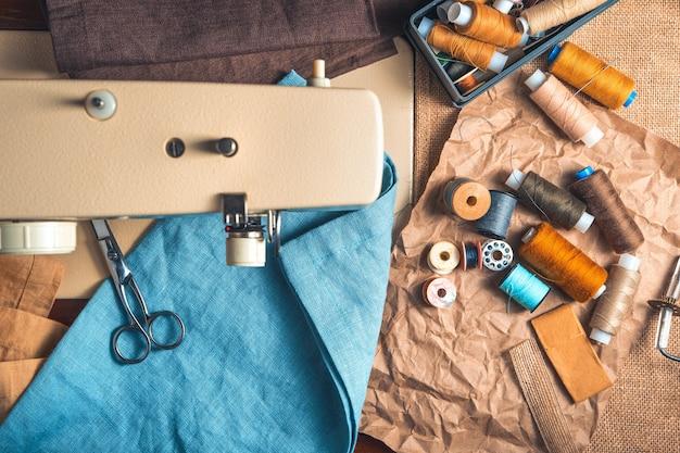 Nici w różnych kolorach, nożyczki, tkaniny na tle rozmytej maszyny do szycia. widok z góry, poziomy.