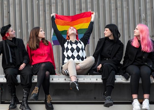 Nie binarni przyjaciele siedzą i trzymają flagę lgbt