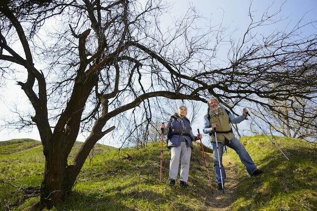 Nie bój się ruszać. starsza rodzina para mężczyzna i kobieta w strój turystyczny spaceru na zielonym trawniku w pobliżu drzew w słoneczny dzień. pojęcie turystyki, zdrowego stylu życia, relaksu i wspólnoty.