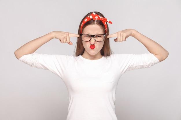 Nie chcę cię słyszeć. portret niezadowolonej emocjonalnej młodej kobiety w białej koszulce z piegami, czarnymi okularami, czerwonymi ustami i opaską. kryty strzał studio, na białym tle na jasnoszarym tle.