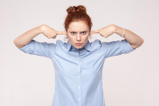Nie chcę od ciebie słyszeć! agresywna kobieta imbir, trzymając palce na uszach i patrząc na kamery. zdjęcia studyjne