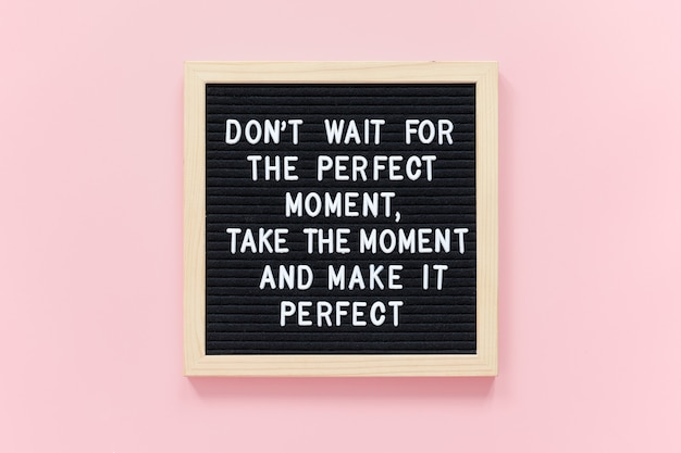 Nie czekaj na idealny moment, weź ten moment i uczyń go idealnym. motywacyjny cytat na ramce czarnej litery