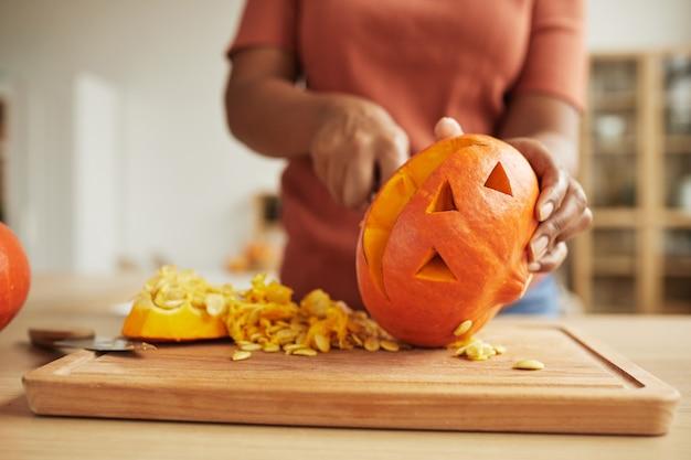 Nie do poznania african american kobieta stojąca przy stole rzeźbiąca jack-o-lantern z dojrzałej dyni pomarańczowy
