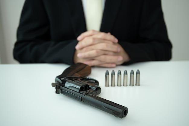 Nie do poznania azjatycki biznesmen wyciągnąć pistolet z uchwytu na broń wewnątrz jego garnituru z bliska. biznesmen lub agent w czarnym garniturze pokazano pistolet rewolwer na stole.