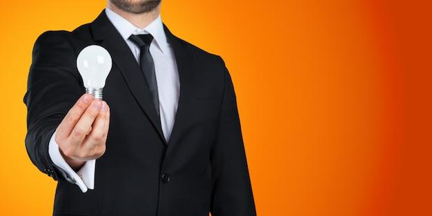 Nie do poznania biznesmen trzyma żarówkę w ręku. pomysł na biznes