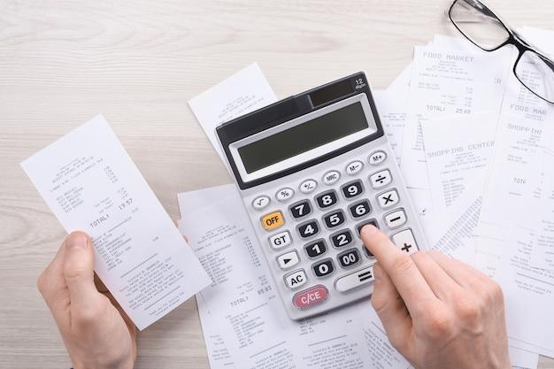 Nie do poznania biznesmen za pomocą kalkulatora na biurku i pisania notatek z obliczeniami o kosztach w domowym biurze. koncepcja rachunkowości finansów. podatki, zakupy, zarządzanie kosztami.