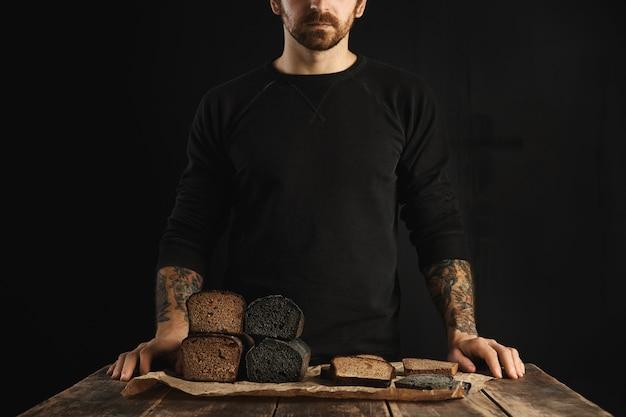 Nie do poznania brodaty wytatuowany mężczyzna sprzedaje świeżo upieczone zdrowe pieczywo dietetyczne