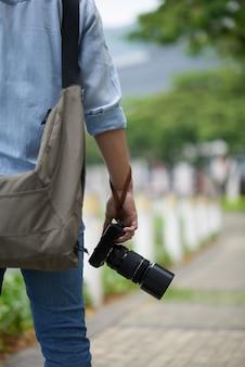 Nie do poznania człowiek z profesjonalnym aparatem fotograficznym stojący w parku