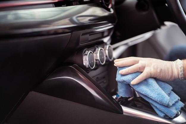 Nie do poznania człowiek za pomocą miękkiej mikrofibry wytrzeć drążek zmiany biegów w nowoczesnym samochodzie, koncepcja usługi opieki samochodowej. pracownik serwisu używający środka dezynfekującego lub środka czyszczącego do sprzątania wnętrza samochodu.