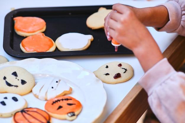 Nie do poznania dziecko dekorujące ciasteczka na halloween
