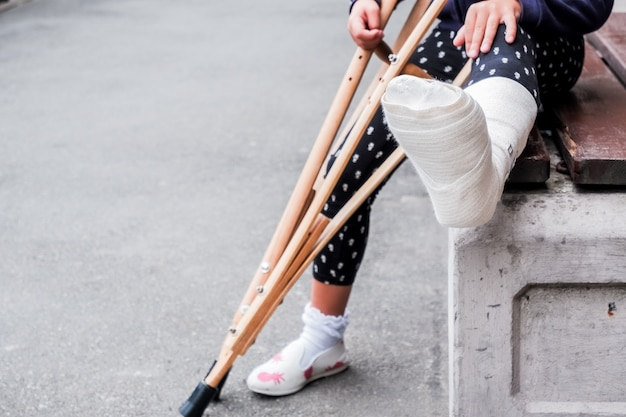 Nie do poznania dziewczyna siedzi na ulicy na ławce ze złamaną nogą i kulami.