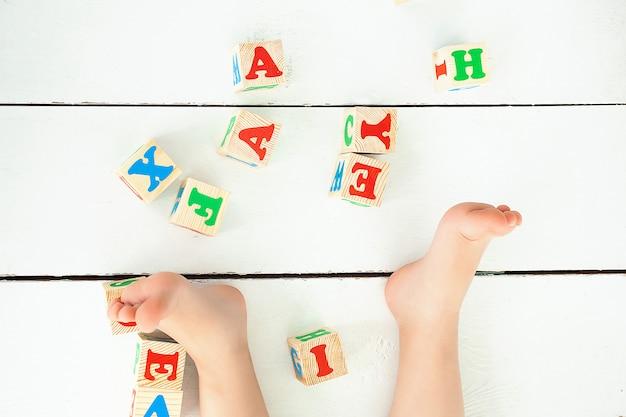 Nie do poznania dziewczynka bawi się kostkami abc w pomieszczeniu. litery na podłodze. tło szkolne