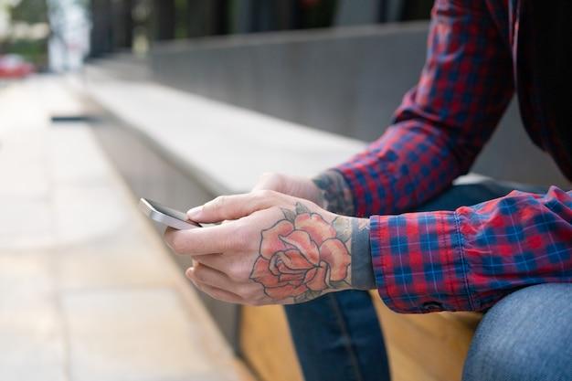 Nie do poznania facet siedzi na drewnianej ławce z telefonem