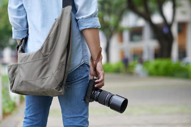 Nie do poznania fotograf stojący w parku i trzymając aparat