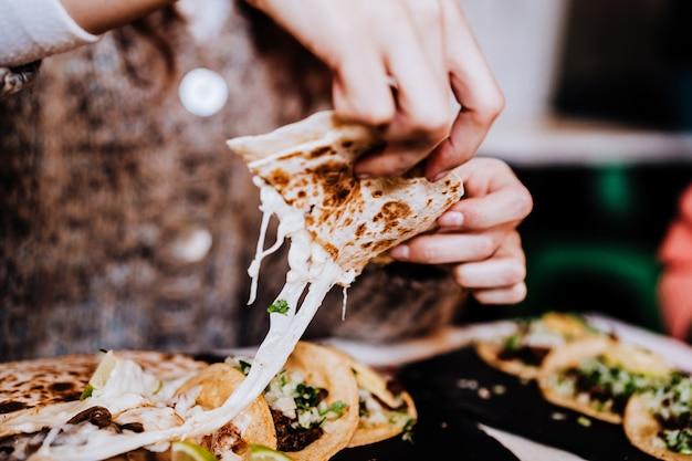 Nie do poznania grupa przyjaciół jedzących meksykańskie jedzenie w restauracji. pyszne fajitas. styl życia na zewnątrz