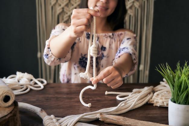 Nie do poznania i szczęśliwa młoda kobieta pokazuje węzeł makramy w obszarze roboczym