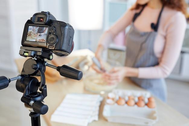 Nie do poznania kobieta blogerka kulinarna gotująca ciasto piekarnicze w aparacie, ujęcie poziome