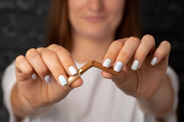 Nie do poznania kobieta łamie papierosa w dłoniach rzucając nałóg