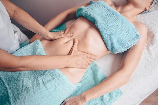 Nie do poznania kobieta leżąca na stole do masażu i korzystająca z masażu leczniczego. dłonie masażysta terapeuta wykonujący masaż antycellulitowy w gabinecie spa.