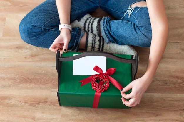 Nie do poznania kobieta otwierająca świąteczny prezent w domu