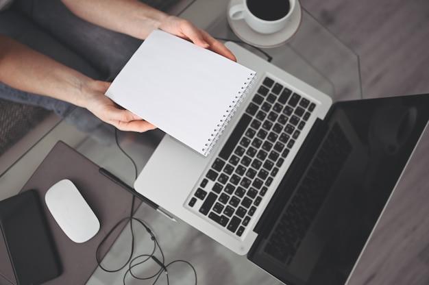Nie do poznania kobieta ręce pisze w pustym notatniku i komputerze. freelancer używa inteligentnego telefonu i laptopa w domu podczas kwarantanny. marketing internetowy, finanse, biznes, koncepcja pracy zdalnej