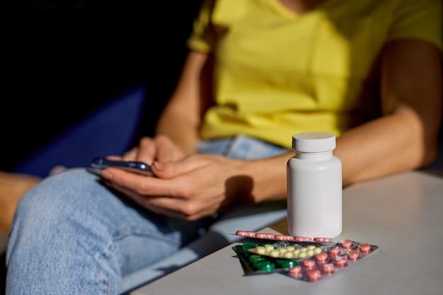 Nie do poznania kobieta siedzi na kanapie z blistrami tabletek za pomocą sklepu apteki internetowej kupując aptekę w internecie zamawiając leki online na smartfonie w domu w słoneczny dzień