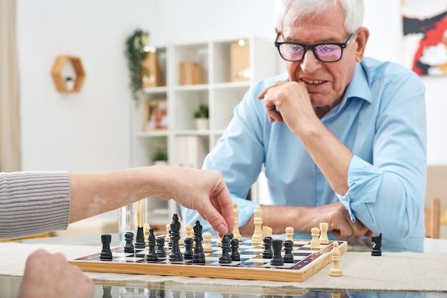 Nie do poznania kobieta siedzi przy stole i gra w szachy z emerytowanym starszym mężczyzną w okularach w domu opieki