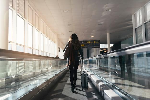 Nie do poznania kobieta spaceru z walizką na lotnisku. pomysł na biznes.