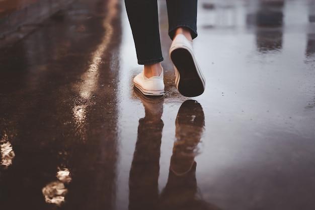 Nie do poznania kobieta spacerująca długą ulicą w deszczu, mokra betonowa droga od burzy