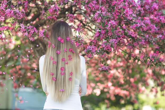Nie do poznania kobieta stojąca tyłem do kamery z długimi blond włosami z kwiatami we włosach. kobieta na tle wiosny. pani na dworze.