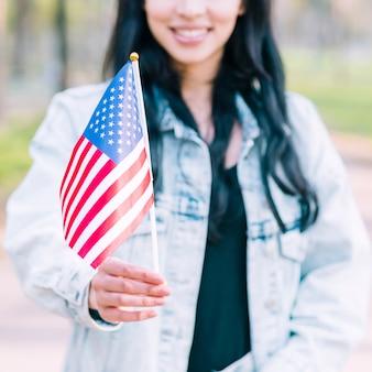 Nie do poznania kobieta trzyma amerykańską flagę podczas obchodów czwartego lipca