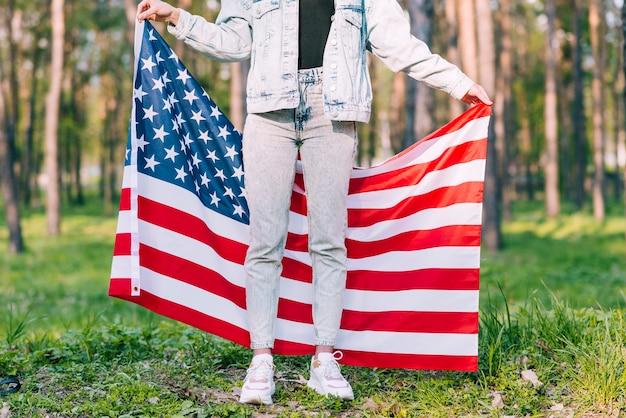 Nie do poznania kobieta trzyma flagę usa za dzień niepodległości