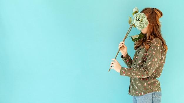 Nie do poznania kobieta trzyma kwiat widok z boku
