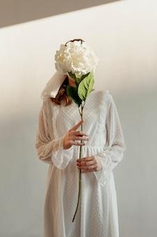 Nie do poznania kobieta trzyma kwiat