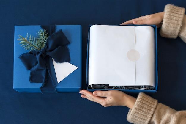 Nie do poznania kobieta trzyma prezent i rozpakowuje w niebieskim pudełku