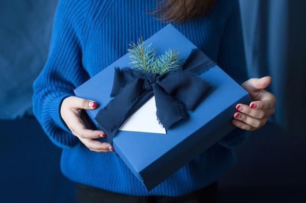 Nie do poznania kobieta trzyma prezent na boże narodzenie w niebieskim pudełku z kokardą