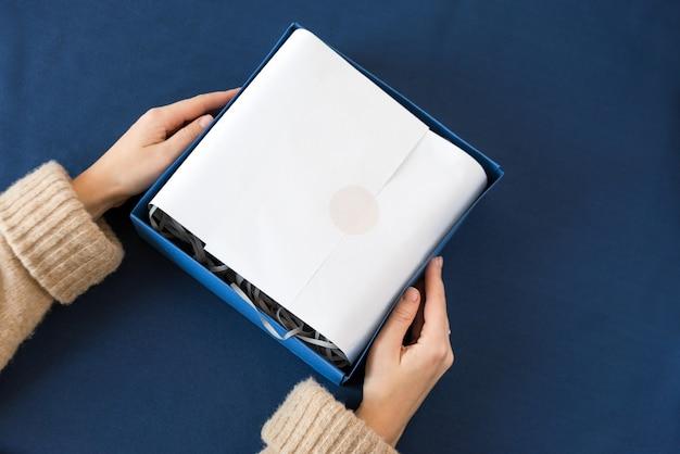 Nie do poznania kobieta trzyma prezent w niebieskim pudełku