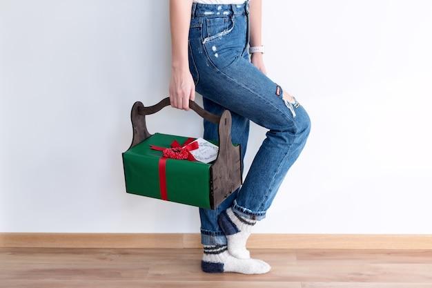 Nie do poznania kobieta trzyma prezenty w drewnianym koszu