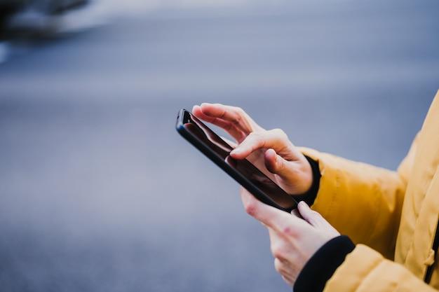 Nie do poznania kobieta turystyczny za pomocą telefonu komórkowego na zewnątrz na ulicy. koncepcja stylu życia i podróży