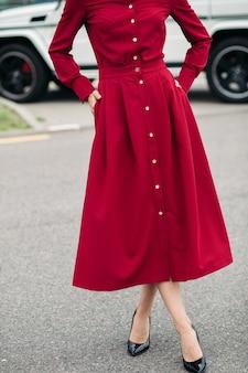Nie do poznania kobieta w czerwonej sukience ze złotymi guzikami i czarnymi szpilkami pozuje na ulicy z rękami w kieszeniach spódnicy.