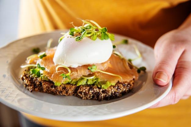 Nie do poznania kobieta w żółtej koszuli trzyma talerz z tostem z łososia, awokado i ułożonym jajkiem