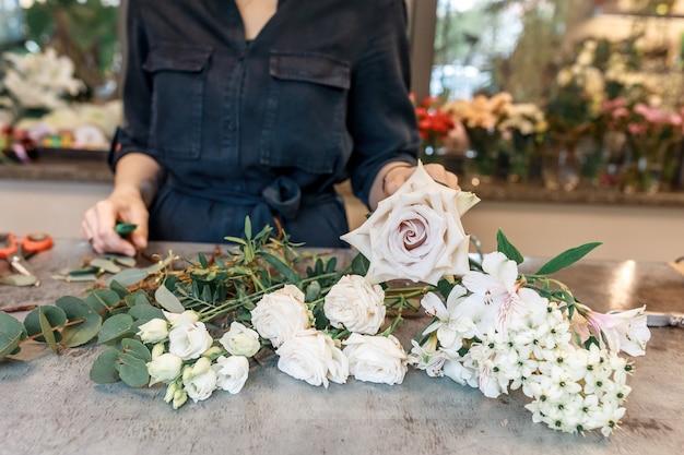 Nie do poznania kobieta zbiera w dłoniach kompozycję kwiatową. koncepcja wystroju i dekoracji świąt z kwiatami.