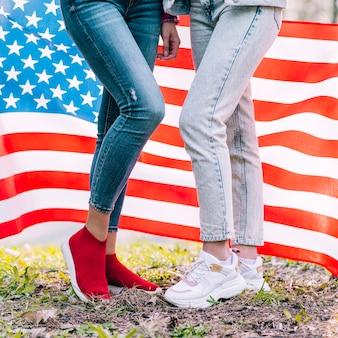 Nie do poznania kobiety stojące na ziemi i trzymając flagę usa za