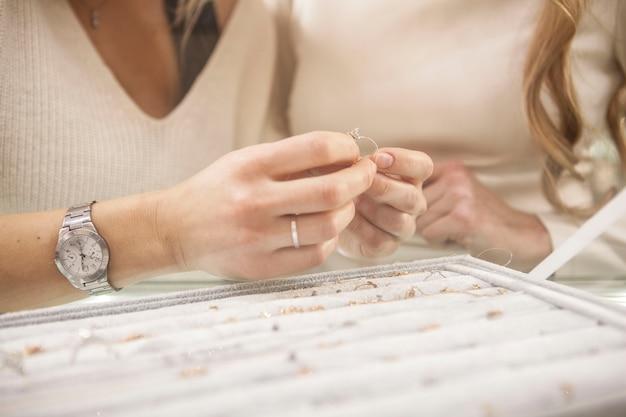 Nie do poznania koleżanki wybierające pierścionki do kupienia w sklepie jubilerskim
