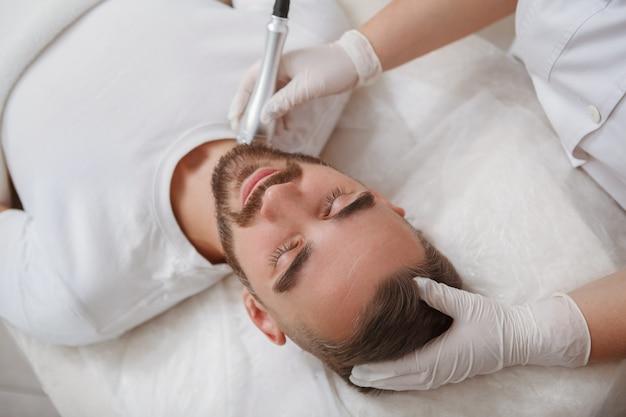 Nie do poznania kosmetolog stosujący rfliftingujący aparat do pielęgnacji skóry szyi klienta