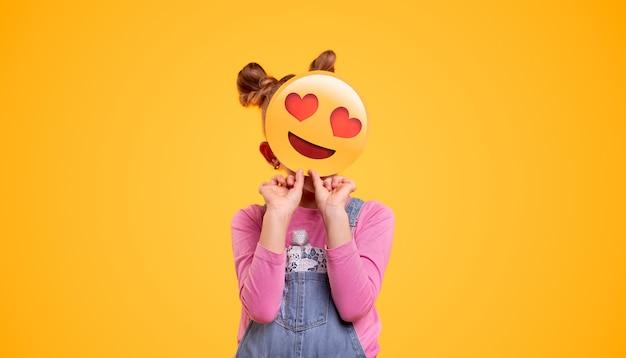 Nie do poznania mała dziewczynka w dżinsowym kombinezonie zakrywającym twarz z uśmiechniętą miłością emotikon, stojąc na jasnożółtym tle