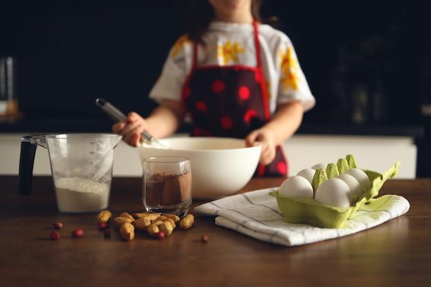 Nie do poznania mała dziewczynka w pomieszczeniu fartuch w kuchni ugniata ciasto na ciasto lub babeczki z kakao i orzechami.