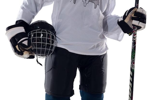 Nie do poznania mężczyzna hokeista z kijem na boisku na lodzie i białym tle. sportowiec noszący sprzęt i ćwiczący kask. pojęcie sportu, zdrowego stylu życia, ruchu, akcji. ścieśniać.