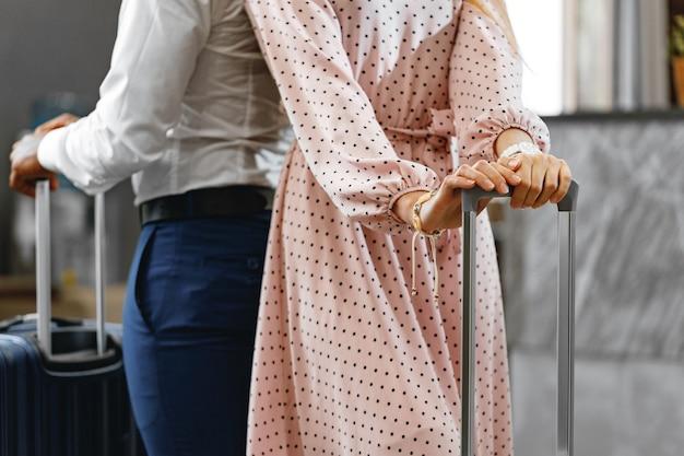 Nie do poznania mężczyzna i kobieta z walizkami stojący w pobliżu recepcji w hotelu z bliska