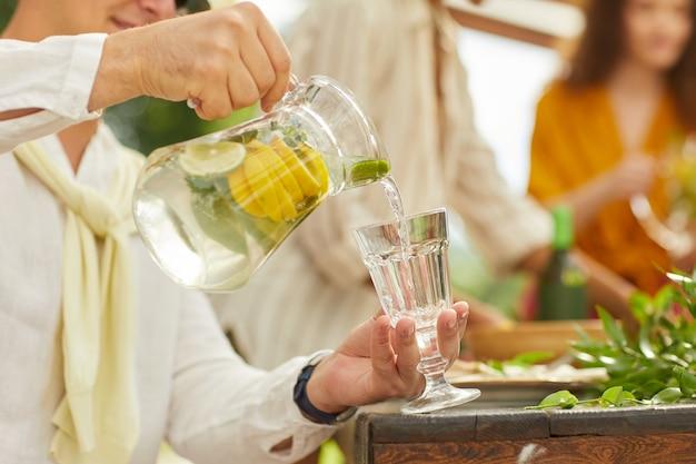 Nie do poznania mężczyzna nalewa lemoniadę do szklanego kubka, ciesząc się letnią imprezą na świeżym powietrzu